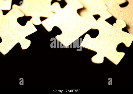Puzzles scattered on a black surface close up. Abstract background - Stock Photo