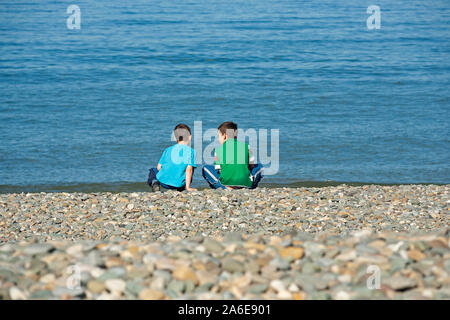 Two young boys are sitting at the beach of Bray in County Wicklow, Republic of Ireland. - Stock Photo