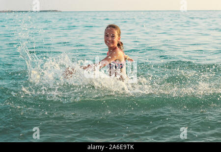 beautiful Teen Girl playing In Sea Waves. Jump Accompanied By Water Splashes. Summer  Day, Happy childhood, Ocean Coast concept - Stock Photo