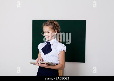 schoolgirl with an tablet in class at the school board - Stock Photo