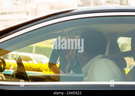 Young women commuter happy to see her Uber arrive - Stock Photo