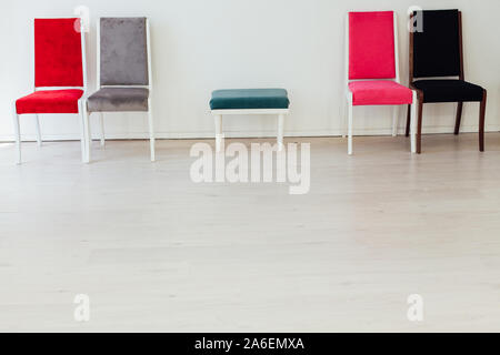 five chairs in an empty white interior room