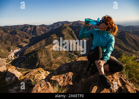 A hiker girl is sitting and drinking fresh water from her blue canteen on the edge of the cliff - She is wearing sunglasses, black leggings and traine - Stock Photo