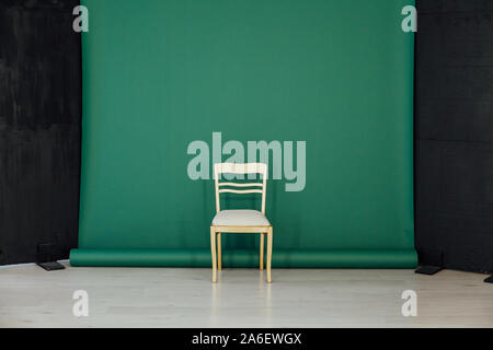 yellow chair in the interior of the room against a green background - Stock Photo