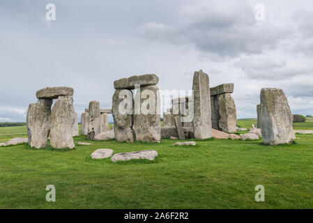 Stonehenge on a cloudy and windy spring day. Ancient ruins in Wiltshire, England, with no people or tourists. Green grass in the foreground - Stock Photo