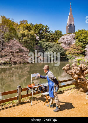 4 April 2019: Tokyo, Japan - Artist painting cherry blossom and the lake in Shinjuku Gyoen National Garden, Tokyo. - Stock Photo