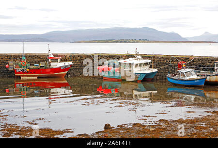 A view of fishing boats tied-up by the pier with reflections and Broadford Bay with Pabay in the background at Broadford, Isle of Skye, UK, Scotland. - Stock Photo