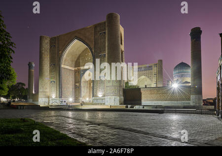 illuminated Bibi-Khanym Mosque or Bibi Khanum Mosque after sunset, Samarkand, Uzbekistan, Central Asia - Stock Photo