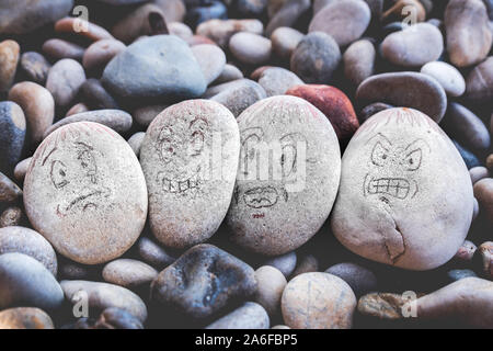 managing emotions emoji faces on stones - sad, happy, surprised worried and angry feelings draw - Stock Photo