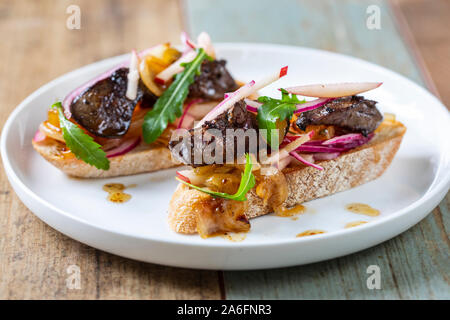 Chicken liver with apple, onion and mango chutney on toast - Stock Photo