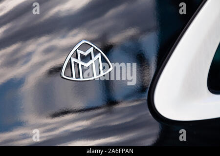 Russia Moscow 2019-06-17 Closeup emblem logo on front of brand Mercedes Maybach S500 dark blue car, sky and city reflection on car bonnet - Stock Photo
