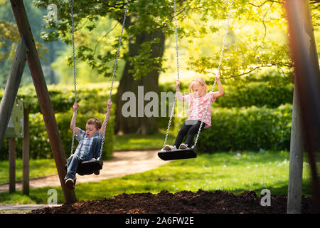 A little boy with ADHD, Autism, Aspergers Syndrome, playing on a swing with his little sister on a beautiful sunny day - Stock Photo