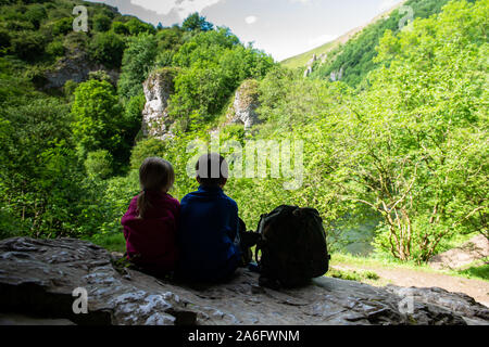 A little boy with ADHD, Autism, Aspergers syndrome, brother and sister sitting in a cave high in the mountain admiring and taking in the view while re - Stock Photo