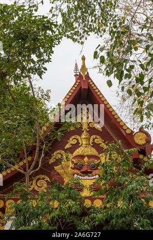 Ko Samui Island, Thailand - March 18, 2019: Wat Khunatam Buddhist Temple and monastery. Maroon gable with golden decorations of scary face, framed by - Stock Photo