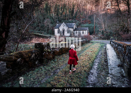 A little girl walking towards an old scary, spooky abandoned house, church in the woods, located in the Derbyshire Peak District National Park, hallow - Stock Photo