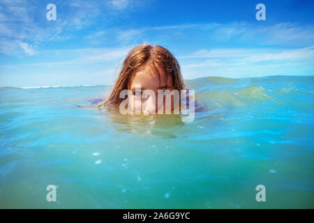 Half underwater portrait of a girl swim in the sea - Stock Photo