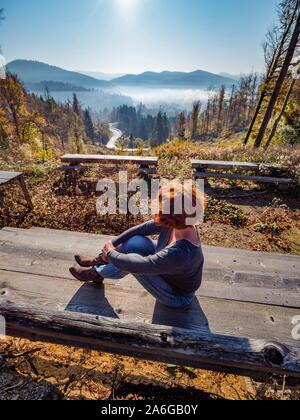 Fit woman is sitting seated on wooden bench in nature against sun sunlight sunshine in nature looking away - Stock Photo