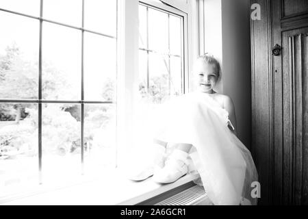 A gorgeous bridesmaid ready for the big day sitting on a windowsill covered in natural light - Stock Photo
