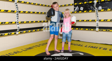 A cute little girl in a boxing ring, mma ring, training with her brother, boxing, kickboxing, martial arts, ADHD, Autism, Asperger Syndrome - Stock Photo