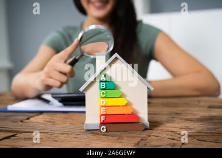 House With Energy Efficiency Rate In Front Of Businessperson Working In Office While Using Calculator - Stock Photo
