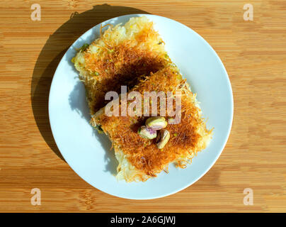 Traditional eastern dessert kunafa. Top view of arabic cheese kunafa in white plate on light wooden  table. Konafa. - Stock Photo