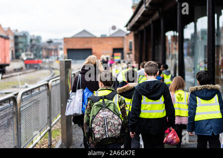 A group of school children walking in the street on a school trip wearing high visibility jackets for safety - Stock Photo