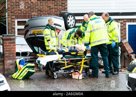 Emergency services on scene at a drink driving accident with an over turned and injured driver, Police, ambulance paramedics and fire brigade, Police - Stock Photo