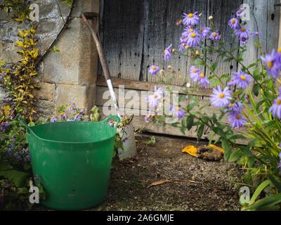 Garden tools are left during the gardener's break beside a wooden door of a sandstone building. - Stock Photo