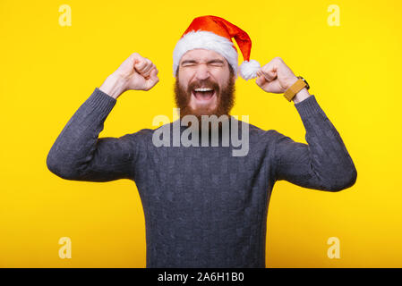 Young cheerful man with beard celebrating success over yellow background, ready for new year - Stock Photo