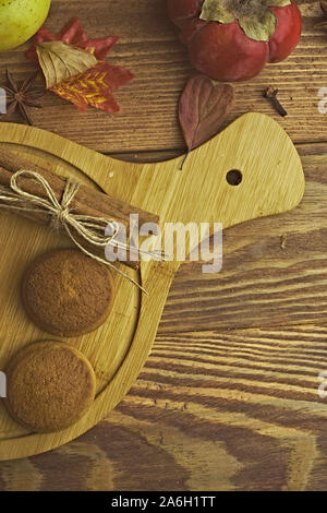 Cookies with pumpkins and apples on the table. Chocolate cookies with apples and pumpkins are on a wooden table. - Stock Photo