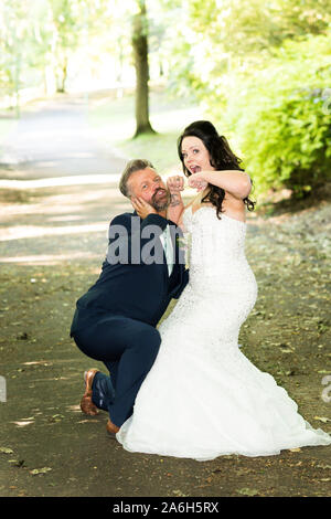 A bride and her brother pose for a funny picture, funny wedding pictures, posing - Stock Photo