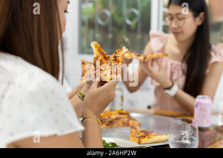 Women with best friends having pizza in restaurant. - Stock Photo