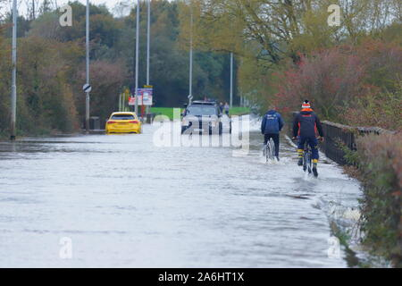 Cyclists battle through floodwater in Castleford after 24 hours of rainfall - Stock Photo