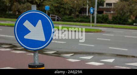 This way roadsign. Road sign one way, blue and round, white color arrow pointing direction right and down, lur street background, copy space - Stock Photo