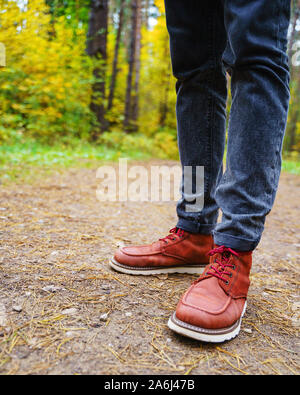 A man in red leather boots walks in the amazing autumn forest. Footwear close up with copy spase. Travel concept. - Stock Photo