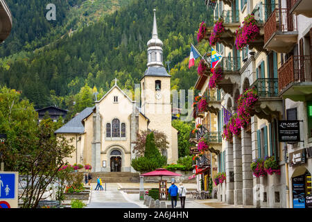 Chamonix Mont-Blanc, France - October 4, 2019: People, autumn street view with catholic church of St Michel in autumn, flowers and houses in town