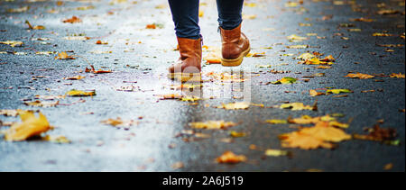 Walk on wet sidewalk. Back view on the feet of a woman walking along the asphalt pavement with puddles in the rain. Pair of shoe on slippery road in t