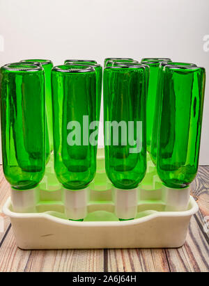 Empty wine bottles in a plastic dryer on the table - Stock Photo