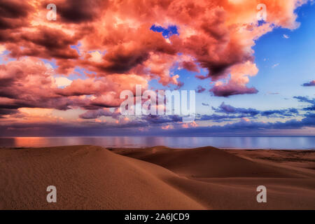 Bright bloody pink clouds over Pacific ocean after rain and storm over sand dunes of Stockton beach in Australia - colourful scenic seascape view. - Stock Photo