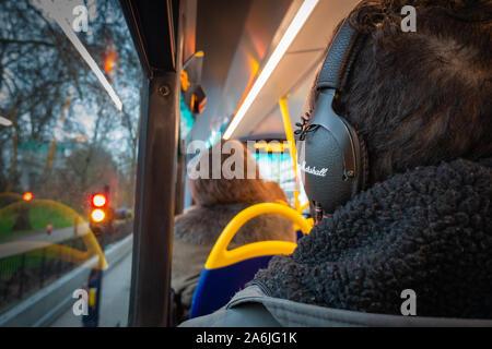 Back of mans head wearing headphones on the top floor of a bus