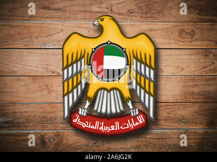 United Arab Emirates coat of arms on wooden background.
