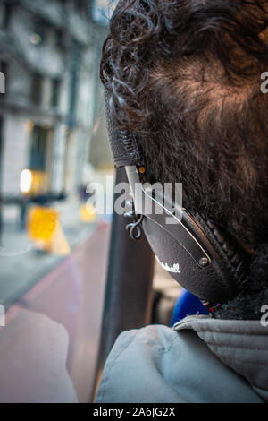 Back of mans head wearing headphones on the top floor of a bus - Stock Photo