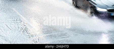 Blurry abstract car driving on flooded street in motion blur with water splash puddle,  background - Stock Photo