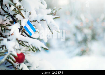 Christmas Nicaragua. Xmas tree covered with snow, decorations and a flag. Snowy forest background in winter. Christmas greeting card. - Stock Photo