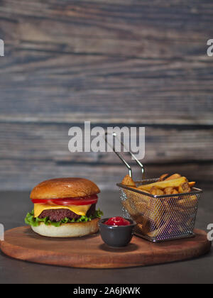 vegan plant based burger with fries and ketchup served on rustic wooden tray - Stock Photo