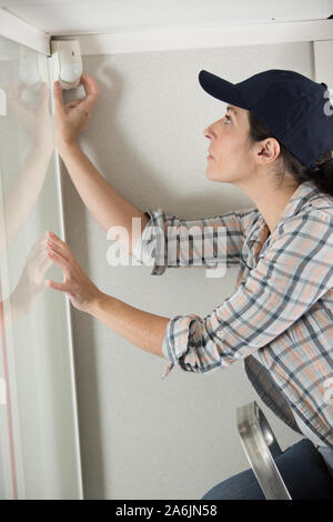 woman installing a burglar alarm - Stock Photo