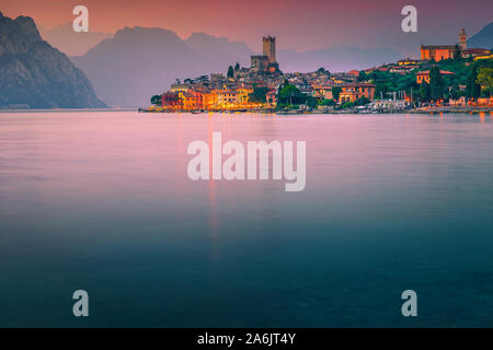 Picturesque summer vacation and touristic resort, Malcesine recreation location, admirable beach at sunset, Garda lake, Veneto region, Italy, Europe - Stock Photo