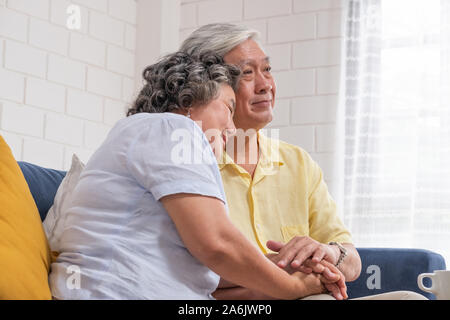 Close up Asian senior couple encouraging together by holding hand each other at sofa in living room at home.Happy retirement lifestyle.aging at home - Stock Photo