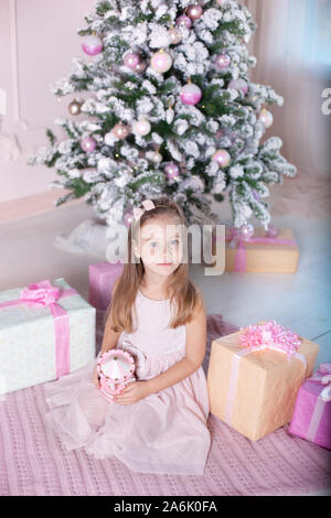 New Year 2020! The concept of Christmas, holidays and childhood. A little girl in a pink dress holds a musical toy carousel near the Christmas tree. - Stock Photo