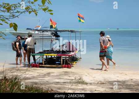 Mauritius tourists; tourists on the beach shopping from a boat stall selling gifts and souvenirs, Ile aux Benitiers, Maurtius